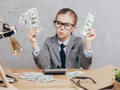 Pensive child holding money in hands